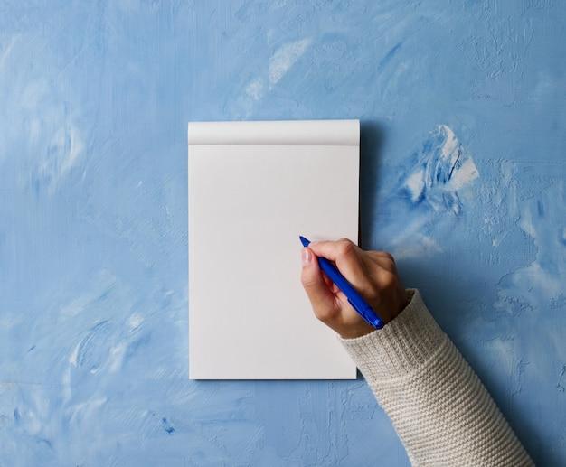 Kobieta pisze w zeszycie na kamiennym niebieskim stole, ręka w koszuli trzyma ołówek,