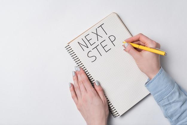Kobieta pisze w zeszycie napis następny krok. odręczny tekst. widok z góry notatnika