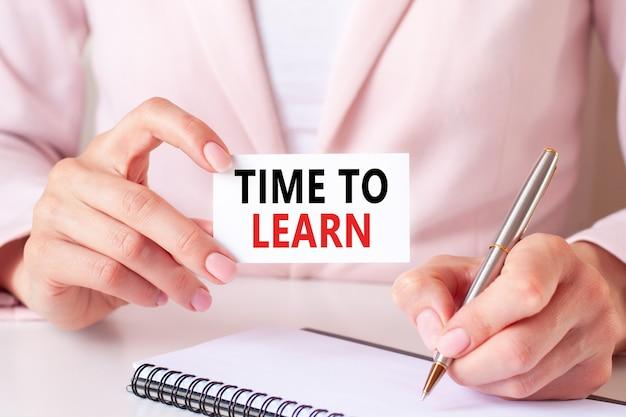 Kobieta pisze w zeszycie srebrnym długopisem i ręką trzymającą karteczkę z tekstem: czas nauczenie