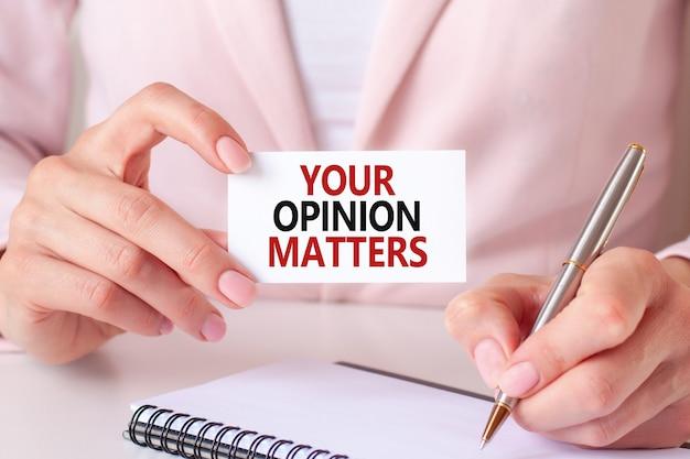 Kobieta pisze w zeszycie srebrnym długopisem i ręką trzymającą karteczkę z tekstem: twoja opinia ma znaczenie