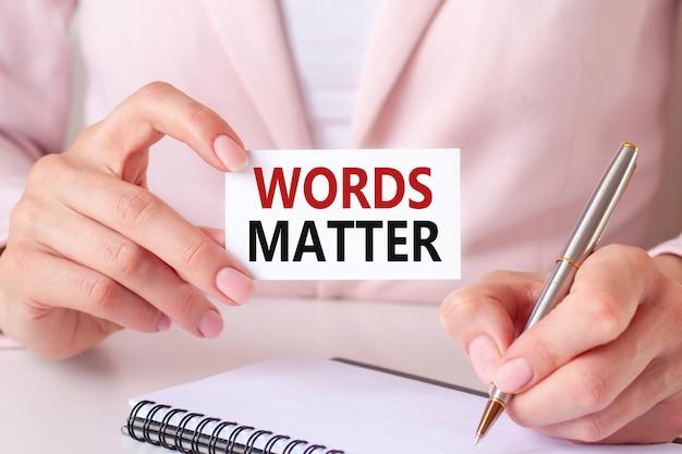 Kobieta pisze w zeszycie srebrnym długopisem i ręką trzymającą kartkę z tekstem: słowa mają znaczenie.