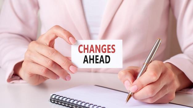 Kobieta pisze w zeszycie srebrnym piórem i ręką trzymającą kartę z tekstem: zmiany w przyszłości.