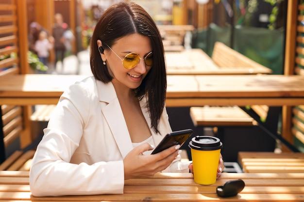 Kobieta pisze wiadomości w swoim smartfonie i słucha muzyki