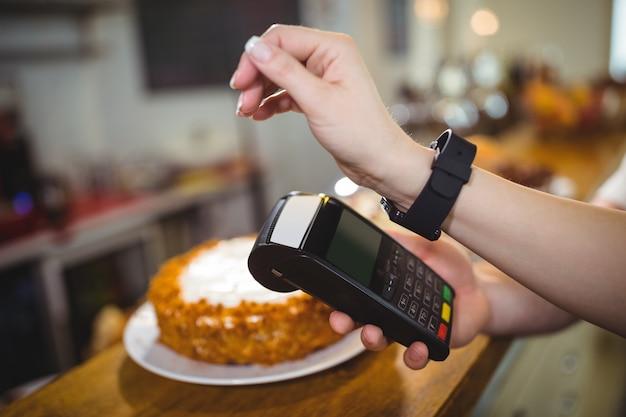 Kobieta płacąc rachunki za pomocą technologii nfc smartwatch