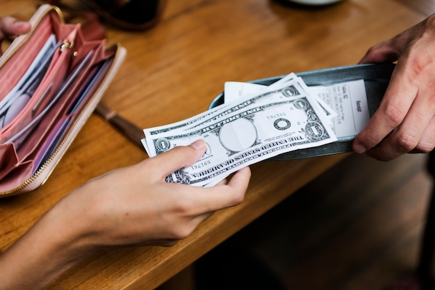 Kobieta płacąca gotówką za restaurację z rachunkami