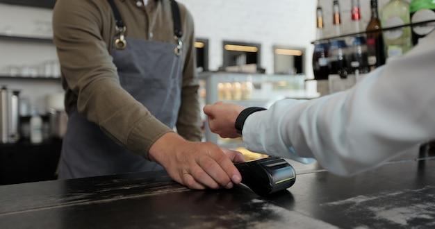 Kobieta płacąca technologią nfc przez smartwatch zbliżeniowy na terminalu w nowoczesnej kawiarni. koncepcja płatności bezgotówkowych.