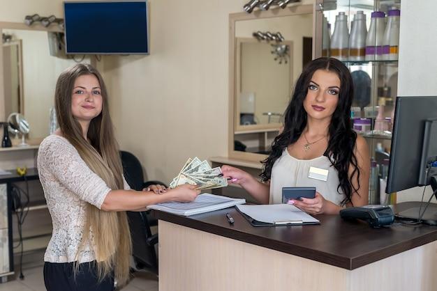 Kobieta płaci dolary administratorowi w gabinecie kosmetycznym