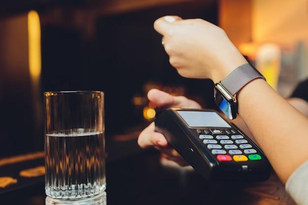 Kobieta płaci inteligentnym zegarkiem z technologią nfc.