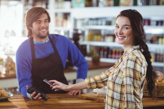 Kobieta płaci rachunek przez smartphone za pomocą technologii nfc