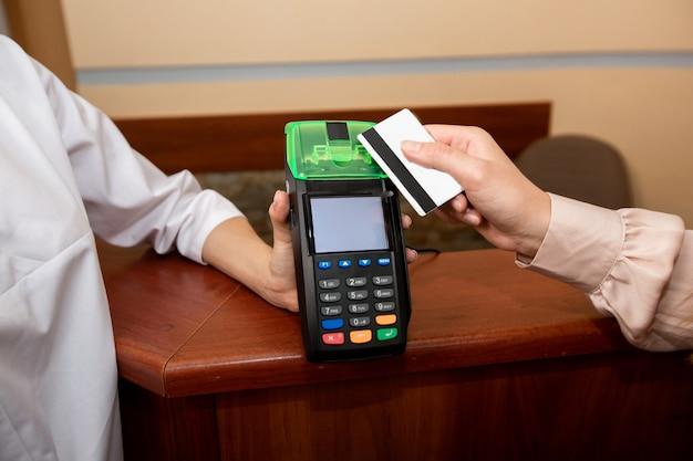 Kobieta płaci za usługi lekarskie kartą kredytową i terminalem
