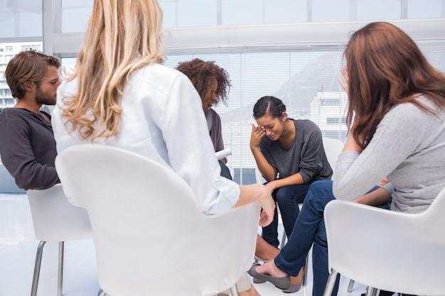 Kobieta płacze w terapii grupowej