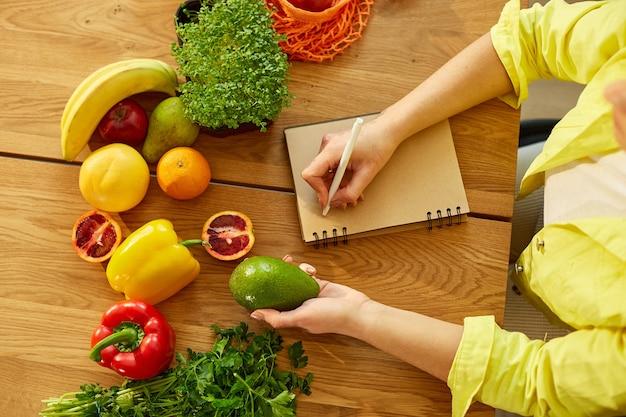 Kobieta, planowanie, pisanie cotygodniowych posiłków na notatce planowania posiłków lub plan diety na drewnianym stole ze zdrową żywnością, owocami i warzywami w jej kuchni w domu.