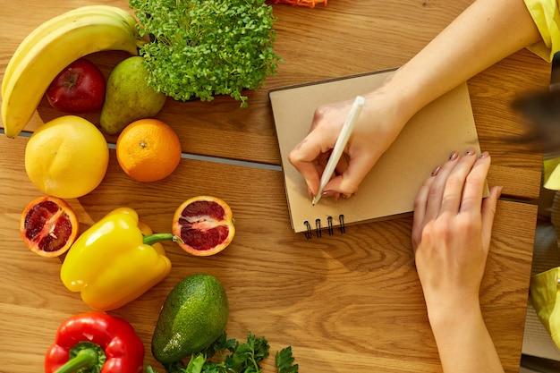 Kobieta planuje, pisze tygodniowe posiłki na notatce planowania posiłków