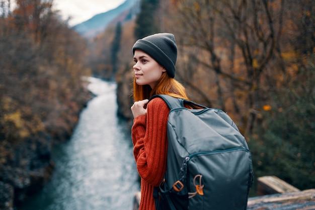Kobieta plecak turystyczny rzeka góry jesień