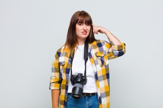 Kobieta plus size czuje się zdezorientowana i zdziwiona, pokazując, że jesteś szalony, szalony lub oszalały