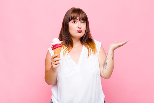 Kobieta plus size czuje się zdziwiona i zdezorientowana, wątpi, waży lub wybiera różne opcje z zabawnym wyrazem twarzy