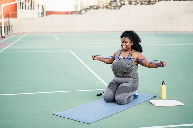 Kobieta plus size robi rutynę treningową na świeżym powietrzu w parku miejskim