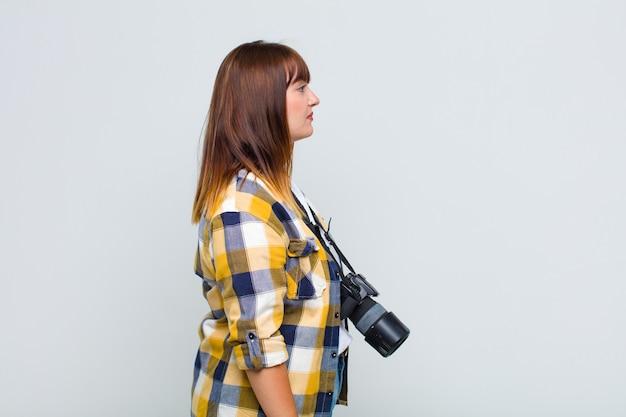 Kobieta plus size w widoku profilu, która chce skopiować przestrzeń do przodu, myśleć, wyobrażać sobie lub marzyć