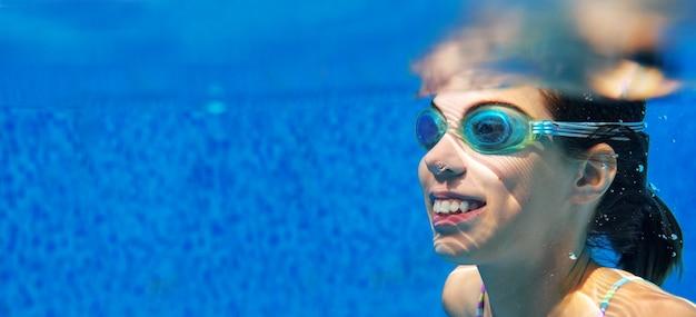 Kobieta pływa pod wodą w basenie, szczęśliwa aktywna nastolatka nurkuje i bawi się pod wodą, fitness dla dzieci i sport na rodzinne wakacje w kurorcie