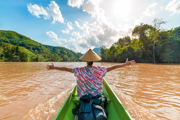 Kobieta pływa tradycyjnym kapeluszem na brown wodzie nam ou rzeka w laos