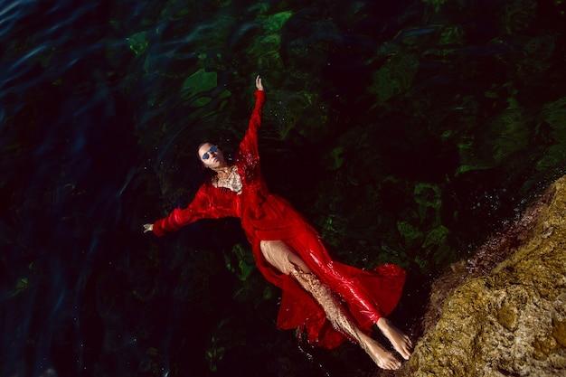 Kobieta pływa w morzu w czerwonej długiej sukni z okularami przeciwsłonecznymi