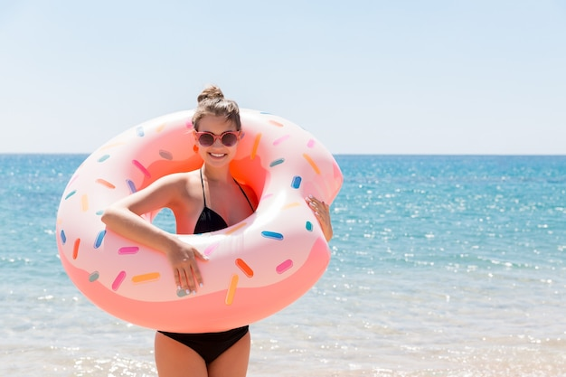 Kobieta pływanie z nadmuchiwanym pączkiem na plaży w słoneczny letni dzień. letnie wakacje i koncepcja wakacji.