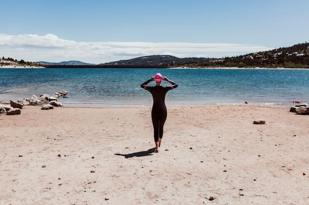 Kobieta po czterdziestce ubrana w neopren i czekająca na kąpiel w jeziorze. koncepcja triathlonu
