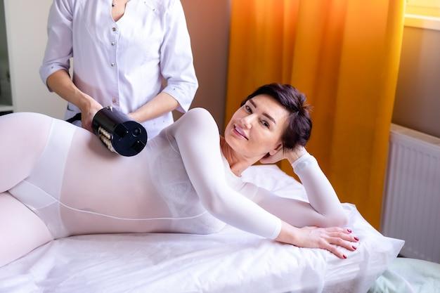 Kobieta po zabiegu masażu antycellulitowego lpg lub r-smooth z aparatem
