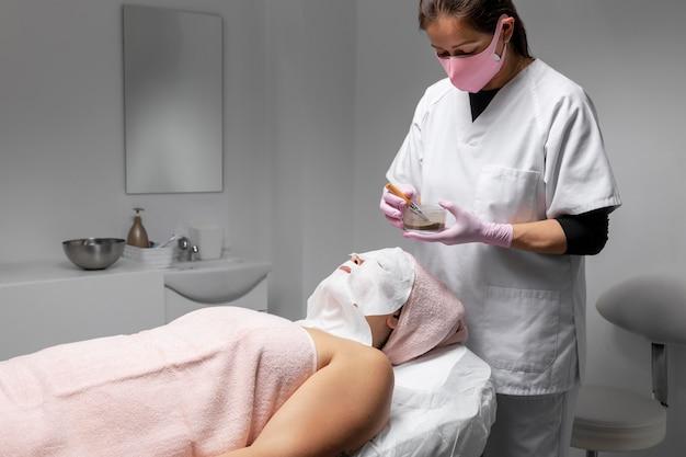 Kobieta po zabiegu na twarz w salonie kosmetycznym