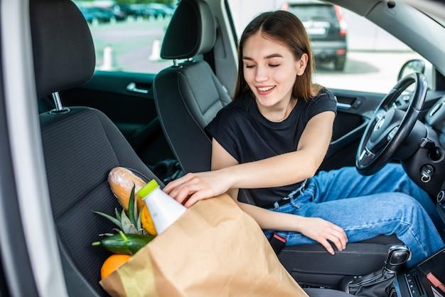 Kobieta po zakupach w centrum handlowym lub w centrum handlowym i wraca do domu samochodem na zewnątrz