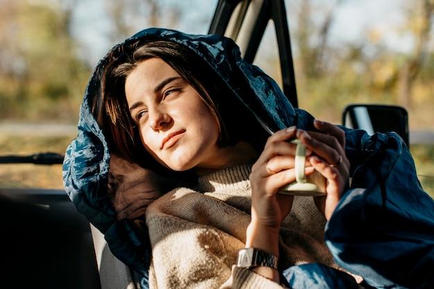 Kobieta pocałowana słońcem, trzymając filiżankę kawy