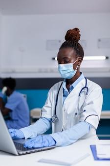 Kobieta pochodzenia afrykańskiego pracująca jako lekarz w gabinecie lekarskim