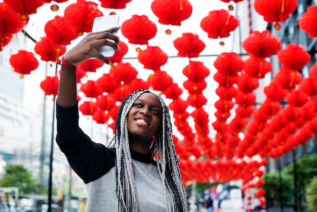 Kobieta pochodzenia afrykańskiego selfies z czerwoną lampą