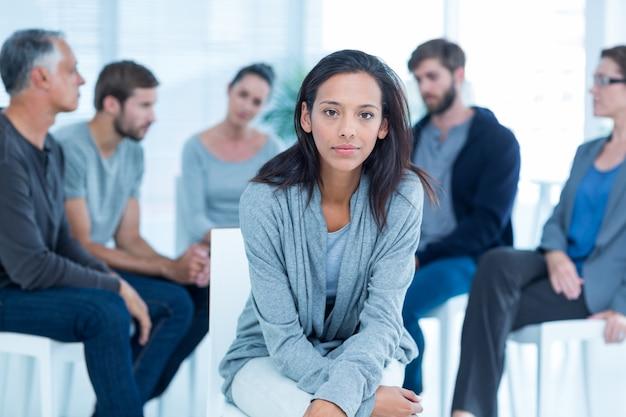Kobieta pocieszająca inna w odwykowej grupie przy terapią