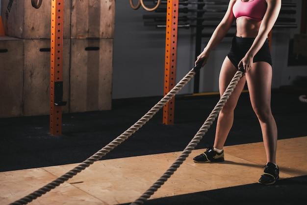 Kobieta, poćwiczyć w siłowni szkolenia robi krzyż dopasowanie ćwiczeń z lin bitewnych