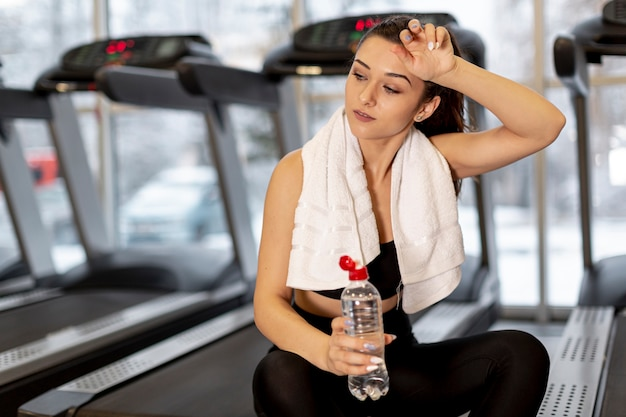 Kobieta pod dużym kątem nawilżająca po treningu