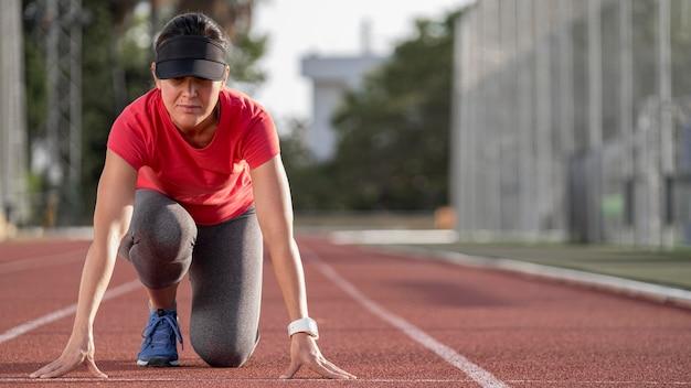 Kobieta pod niskim kątem gotowa do biegu