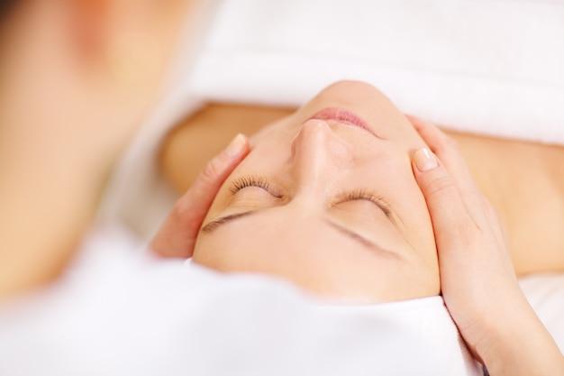 Kobieta pod profesjonalnym masażem twarzy w beauty spa