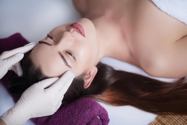 Kobieta pod profesjonalnym masażem twarzy w spa