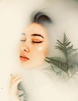 Kobieta pod wodą z liśćmi paproci