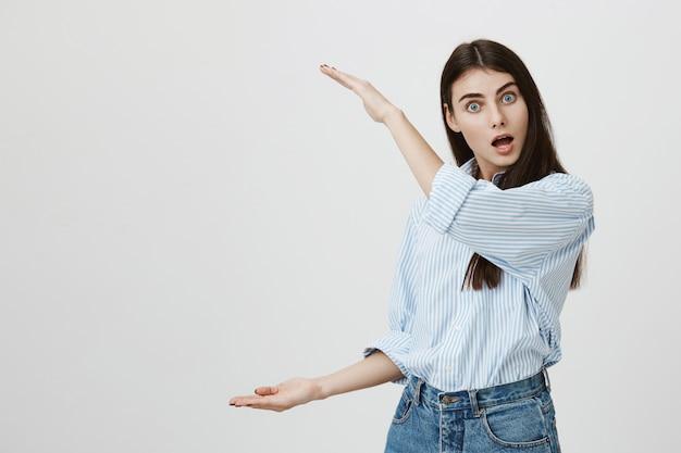 Kobieta pod wrażeniem pokazująca coś dużego, dużego przedmiotu