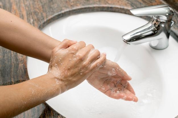 Kobieta pod wysokim kątem do mycia rąk