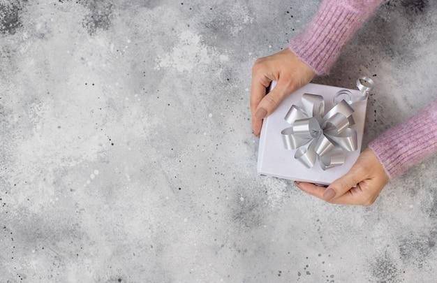 Kobieta podająca białe pudełko ze srebrną kokardką
