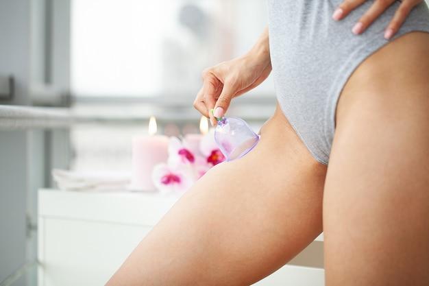 Kobieta podczas masażu antycellulitowego bioder puszkami próżniowymi w gabinecie kosmetycznym.