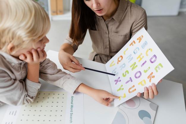 Kobieta podczas terapii mowy z małym chłopcem w swojej klinice