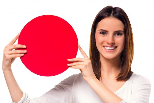 Kobieta podczas traktowania trzyma round czerwonego znaka dla teksta.