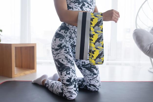 Kobieta podczas treningu fitness w domu z gumową opaską
