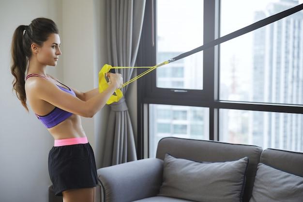 Kobieta podczas treningu w domu z paskami zawieszenia