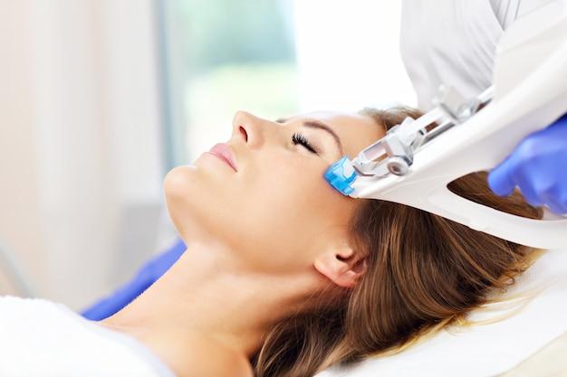 Kobieta poddawana mezoterapii twarzy w salonie kosmetycznym