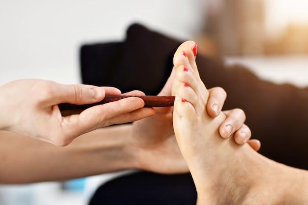 Kobieta poddawana tajskiemu masażowi stóp w spa